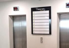 panneau positionné entre les ascenseur de l'immeuble de bureaux